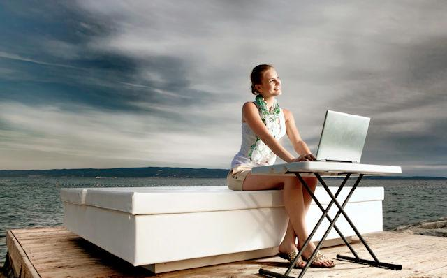 Person with laptop by sea