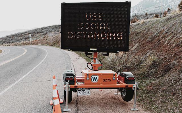 Use Social Distancing sign by road